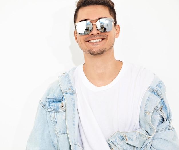 Portrait d'un homme beau jeune mannequin souriant vêtu de vêtements jeans en posant des lunettes de soleil. isolé