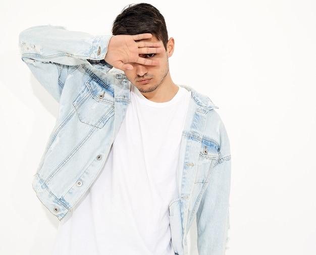 Portrait d'un homme beau jeune mannequin vêtu de vêtements jeans posant. isolé