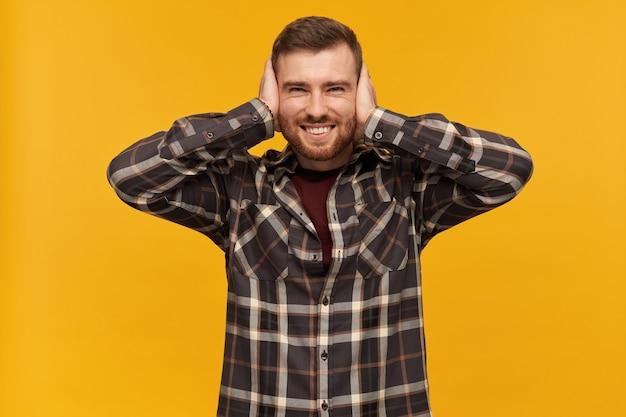 Portrait d'un homme beau et joyeux avec des cheveux et des soies brune. porter une chemise à carreaux et des accessoires. couvrez les oreilles avec des paumes. je ne peux pas entendre. isolé sur mur jaune