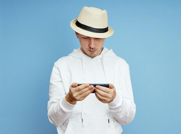 Portrait d'un homme blogueur avec un téléphone dans sa main communiquant sur un smartphone, appel vidéo