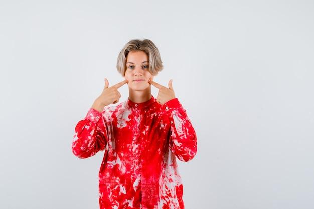 Portrait d'un homme blond de l'adolescence en appuyant sur les doigts sur les joues en chemise surdimensionnée et à la vue de face pensive