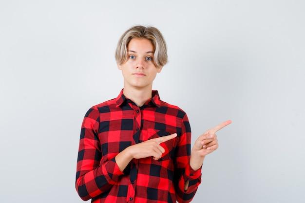 Portrait d'un homme blond de l'adolescence pointant vers le coin supérieur droit en chemise décontractée et regardant la vue de face pensive