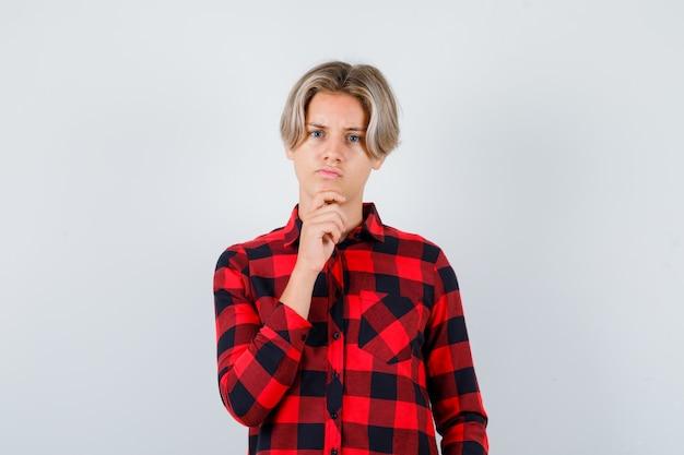 Portrait d'un homme blond adolescent debout dans une pose de réflexion en chemise décontractée et à la vue de face perplexe