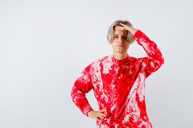 Portrait d'un homme blond adolescent avec la main sur la tête en chemise surdimensionnée et à la vue de face focalisée
