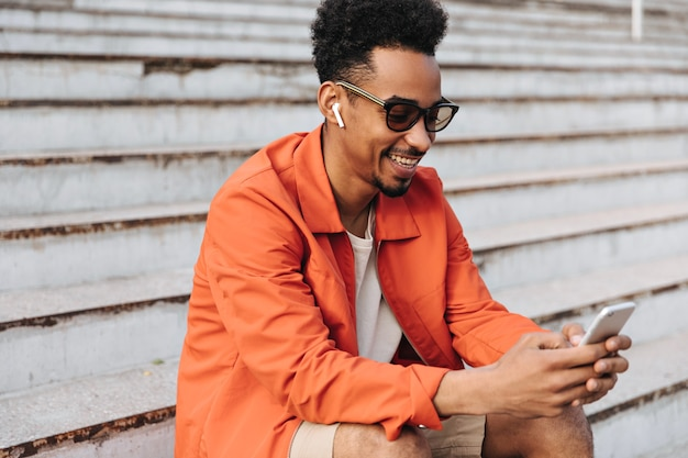Portrait d'un homme bouclé à la peau foncée en veste orange et lunettes de soleil souriant sincèrement et tenant le téléphone