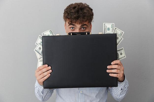 Portrait d'un homme bouclé vêtu d'une chemise souriant tout en tenant un diplomate avec un tas d'argent en espèces isolé sur un mur gris