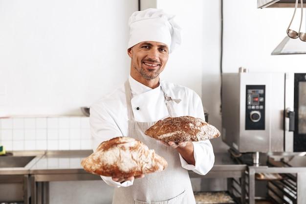 Portrait d'homme boulanger en uniforme blanc debout à la boulangerie, et tenant du pain