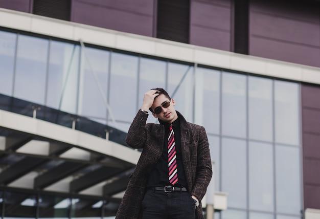 Portrait homme branché en manteau élégant posant dans la ville