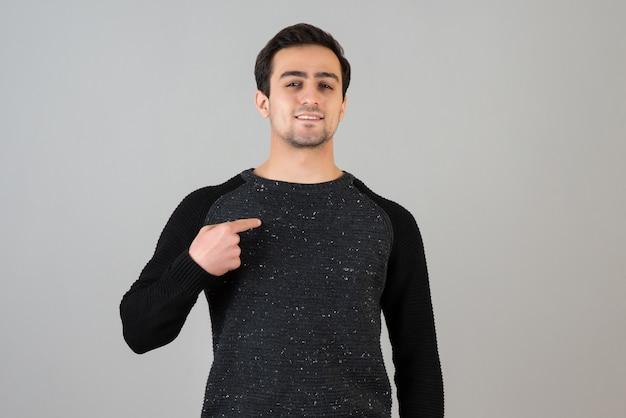Portrait d'un homme brune debout et posant sur un mur gris