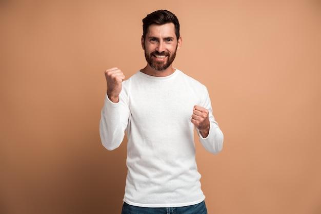 Portrait d'un homme brune extatique avec une barbe montrant que oui, je l'ai fait un geste et un espace de copie joyeux pour l'annonce. studio intérieur tourné isolé sur fond beige