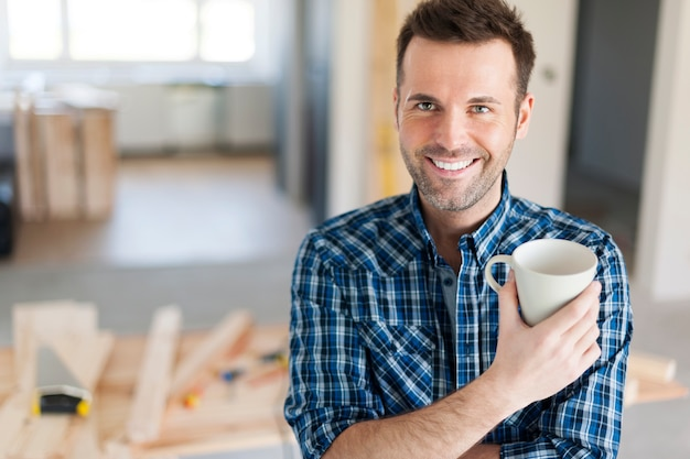 Portrait d'homme buvant du café côté construction