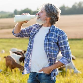Portrait homme buvant du lait de chèvre