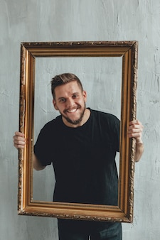 Portrait d'un homme avec un cadre contre un mur gris