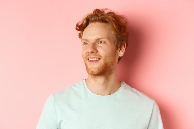 Portrait d'un homme caucasien attrayant avec des cheveux et une barbe en désordre rouge, tourner la tête et à gauche avec un sourire heureux, debout sur fond rose.