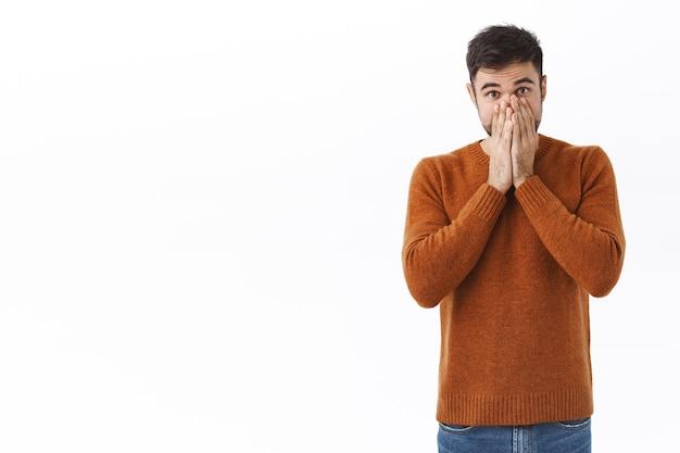 Portrait d'un homme caucasien barbu choqué et sans voix, haletant, couvrant la bouche avec les mains et regardant fixement, se sentant mal à l'aise et troublé, debout préoccupé par le mur blanc