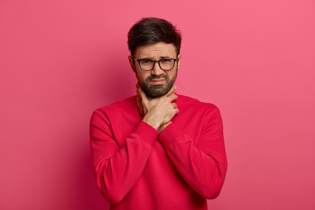 Portrait d'un homme caucasien barbu malheureux se cale, ne peut pas respirer, étouffe et garde les mains sur le cou, fronce les sourcils, souffre de maux de gorge et d'asthme