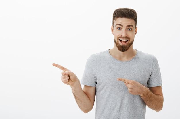 Portrait d'un homme caucasien beau et enthousiaste pointant vers la gauche et parlant avec étonnement et enthousiasme à propos de l'espace de coworking parfait qu'il a trouvé invitant à se joindre au mur blanc