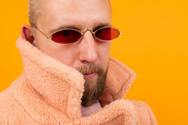 Portrait d'un homme caucasien brutal aux cheveux bleus courts et des lunettes rouges dans un manteau de fourrure isolé sur orange