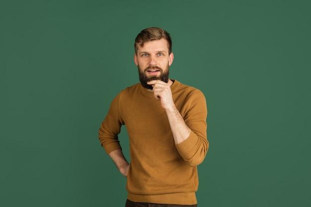 Portrait d'homme caucasien isolé sur mur vert avec copyspace