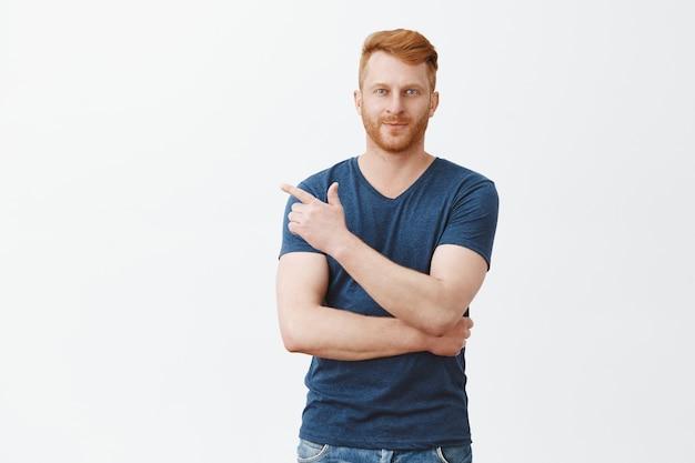Portrait d'un homme caucasien rousse charmant confiant avec poils en tenue décontractée, pointant vers le coin supérieur gauche