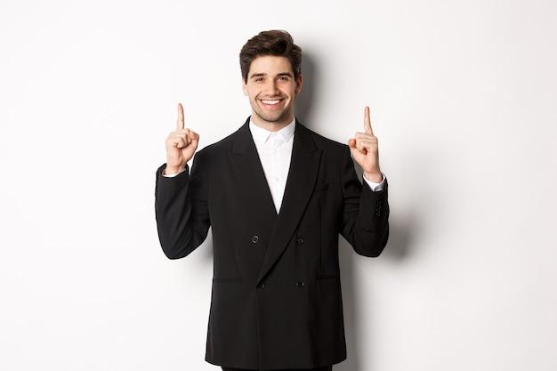 Portrait d'un homme caucasien séduisant en costume noir élégant, pointant les doigts vers le haut et souriant, montrant une publicité de noël, debout sur fond blanc.