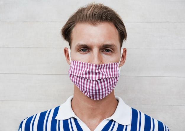 Portrait d'un homme caucasien souriant tout en portant un masque de protection pour la prévention de la propagation du coronavirus