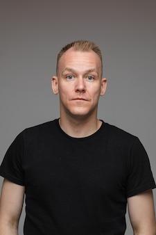 Portrait d'homme caucasien en t-shirt noir regarde la caméra et sourit
