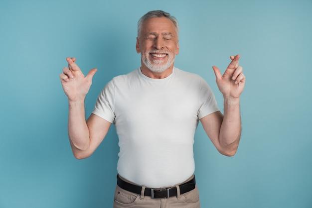 Portrait d'un homme charmant avec barbe levant les bras avec les doigts croisés et souriant