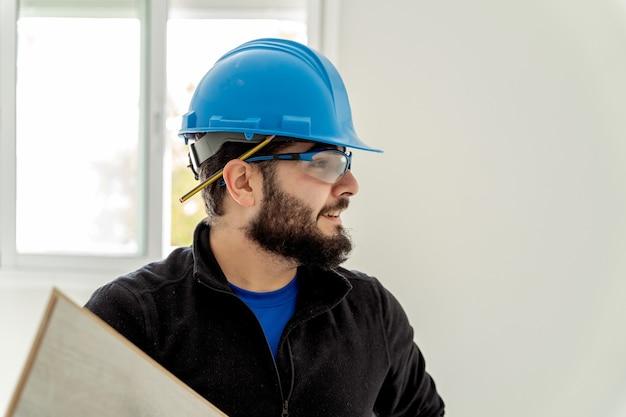 Portrait d'un homme charpentier dans un casque de protection