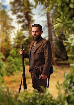 Portrait d'homme chasseur pané en vêtements de chasse traditionnels avec vieux fusil sur forêt verte