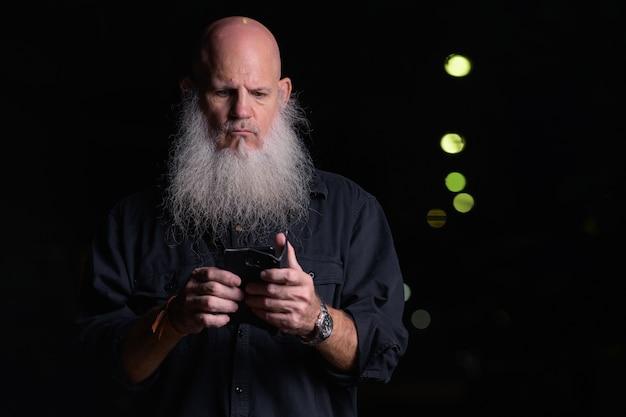 Portrait d'un homme chauve beau mature avec barbe grise à l'extérieur pendant la nuit