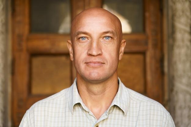 Portrait d'un homme chauve dans le contexte d'un modèle de construction en gros plan sur des yeux bleus et une chemise légère...