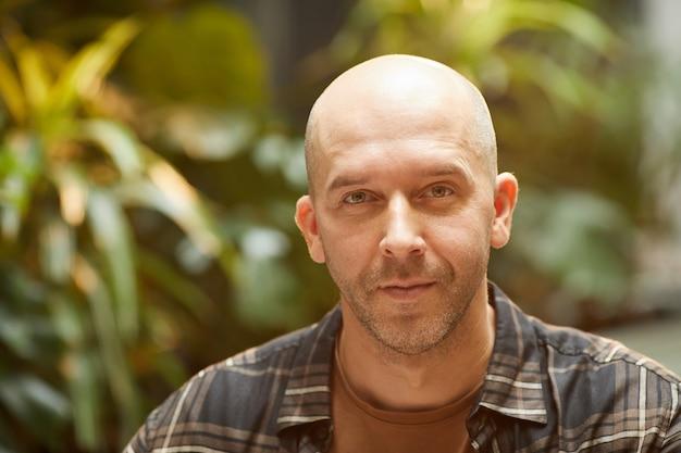 Portrait d'homme chauve mature en chemise à la recherche