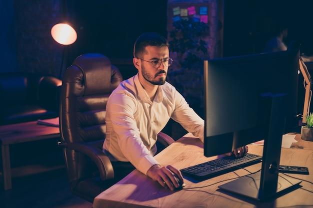 Portrait de l'homme concentré assis sur la table de travail sur ordinateur