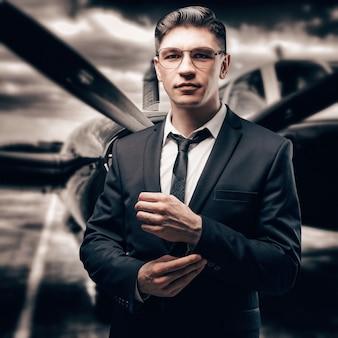 Portrait d'un homme en costume d'affaires. il se tient à l'aéroport au milieu d'un avion de sport. concepteur d'avions. compagnies aériennes privées. technique mixte