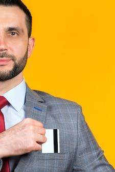 Portrait d'un homme en costume d'affaires qui met une carte bancaire dans sa poche poitrine sur jaune