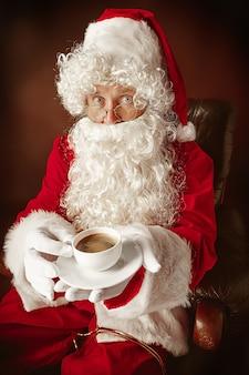 Portrait d'homme en costume de père noël - avec une barbe blanche luxueuse, un chapeau du père noël et un costume rouge au fond de studio rouge assis sur une chaise avec une tasse de café
