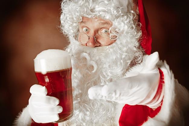 Portrait d'homme en costume de père noël - avec une barbe blanche luxueuse, un chapeau du père noël et un costume rouge au fond de studio rouge avec de la bière