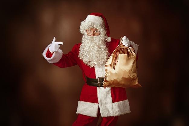 Portrait d'homme en costume de père noël - avec une barbe blanche luxueuse, un chapeau du père noël et un costume rouge sur fond de studio rouge avec des cadeaux