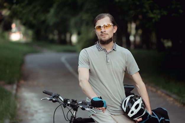 Portrait d'homme cycliste debout à l'extérieur en été chaud contre la route forestière