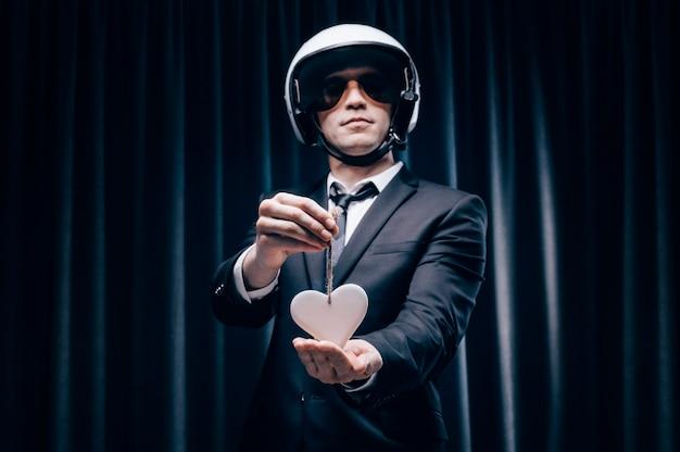 Portrait d'un homme dans un casque. il se tient derrière un rideau dans la cabine et montre aux passagers une forme de cœur