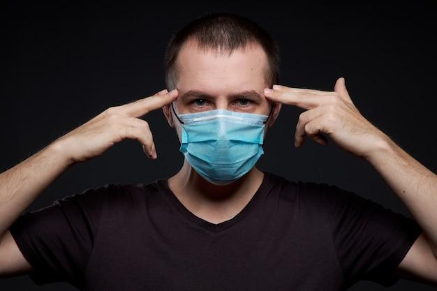 Portrait d'un homme dans un masque médical sur l'obscurité, une infection à coronavirus