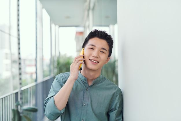 Un portrait d'homme debout sur un balcon en train de passer un appel téléphonique.