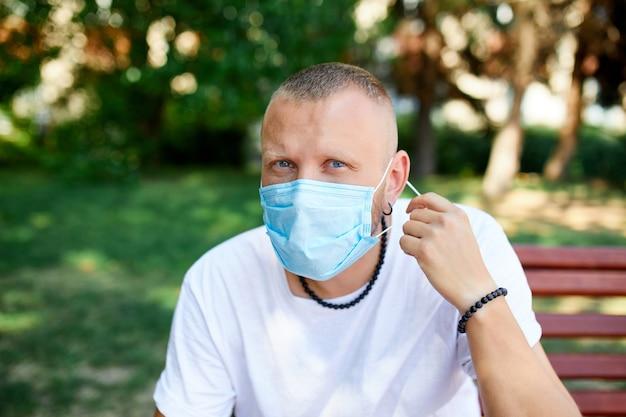 Portrait d'homme décolle un masque de protection dans le parc en plein air dans la ville, concept selfcare