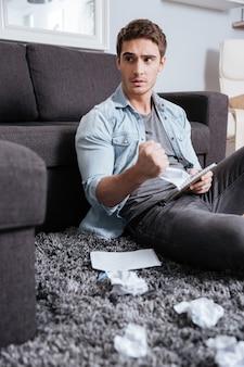 Portrait d'un homme décontracté confus tenant une feuille de papier froissée avec un bloc-notes alors qu'il était assis sur un tapis à la maison