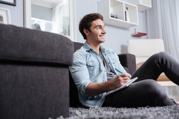 Portrait d'un homme décontracté souriant prenant des notes dans un cahier tout en étant assis sur le tapis à la maison
