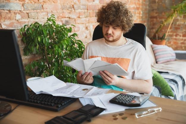 Portrait d'homme de désespoir et de désespoir caucasien regarder des graphiques financiers et économiques pendant la quarantaine des coronavirus, problèmes