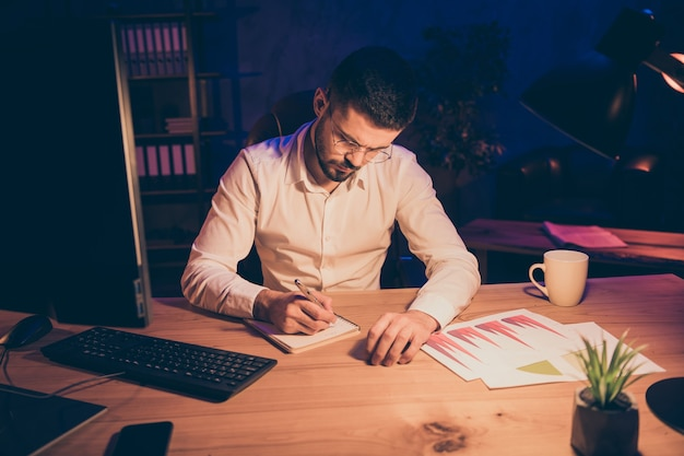 Portrait d'homme de directeur créatif s'asseoir bureau de table écrire dans un cahier