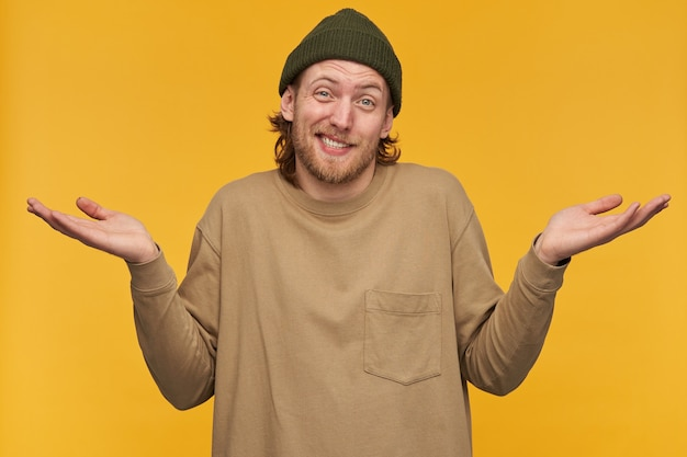 Portrait d'homme douteux et confus aux cheveux blonds et à la barbe. porter un bonnet vert et un pull beige. hausser les épaules avec les mains levées et le visage ironique. isolé sur mur jaune