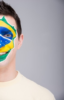 Portrait d'homme avec drapeau brésilien peint sur son visage.